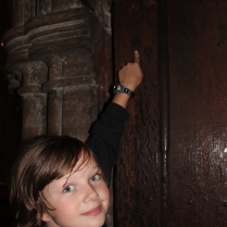 Josiah pointing out bullet holes in the priest's apartment doors from the 1500s (I think?)